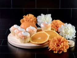Mini orange creamsicle cupcakes with orange and white swirled frosting on a wooden cutting board with a fresh orange sliced next to it and white and orange artificial flowers on a black background.