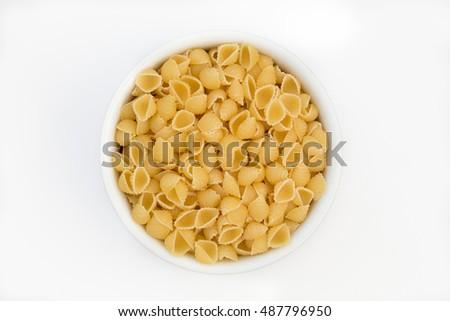 Mini pasta shells in a round white bowl on a white background #487796950