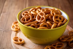 Mini pretzels with salt in a bowl on wooden background. Selective focus.