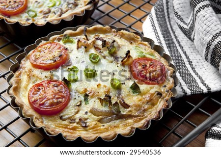 Mini quiches or flans, cooling on wire rack.  Quiche Lorraine, with eggs, cream, tomatoes, onions.
