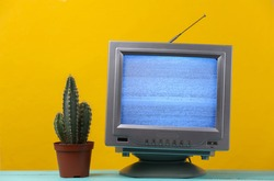 Mini Retro tv antenna receiver on yellow background. Old fashioned TV set with cactus. Television noise, no signal. 80s