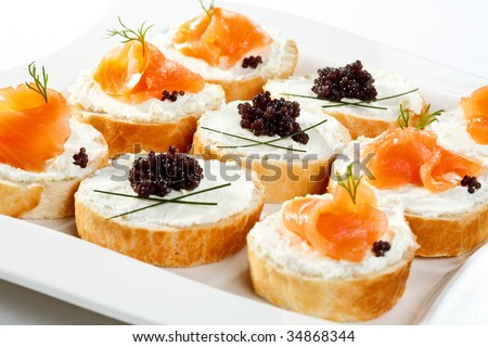 Mini sandwiches - bread with cream cheese, smoked salmon, caviar and vegetables