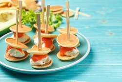 mini sandwiches for a festive treat , made of pancake, cream cheese, salmon and avocado. Buffet snack on a plate, on a blue wooden background, close up, with space