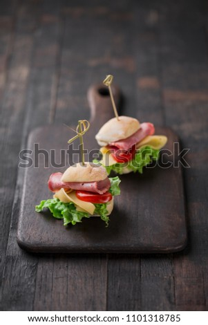 Mini sandwiches with lettuce, tomato, yellow cheese and ham.