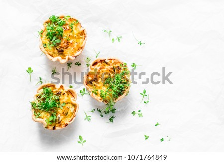 Mini savory pie with chicken, leek, cheese on light background, top view. Delicious appetizer, snack, breakfast, tapas