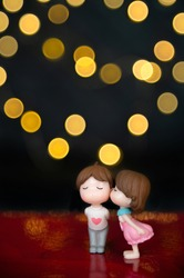 Mini-sculptures of a girl and a boy, she kisses him. Yellow or gold  bokeh on a dark background. Be my Valentine