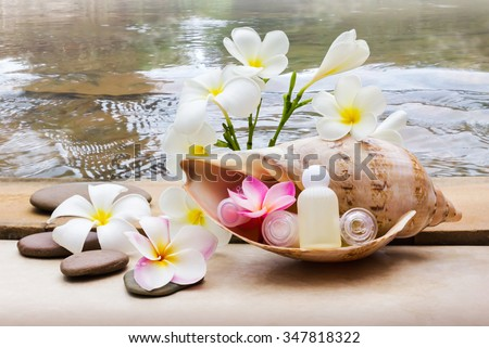 Mini set of bubble bath and shower gel decorated in sea conch shell with pebble rock and flower with crystalline water background, relaxing shower spa in nature concept #347818322