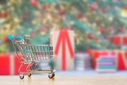 Mini shopping cart on wood table with background blurry of christmas tree and many presents' boxest. blackfriday and shopping online concept.