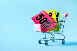 Mini shopping cart with a fifty percent discount sign on blue background. Conceptual image of sale, seasonal discounts in shopping stores.