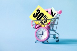 Mini shopping cart with a thirty percent discount sign and pink alarm clock on blue background. Conceptual image of sale, seasonal discounts in shopping stores, discount time