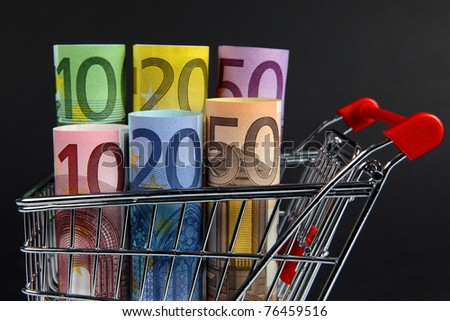 Mini shopping cart with euro banknotes on dark background