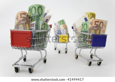 Mini shopping carts with euro banknotes on white background
