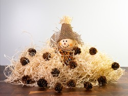 Mini Stuffed Scarecrow with burlap hat Sitting in Pile of Straw with mini pine cones scattered about.  Fall, autumn, Halloween decor.