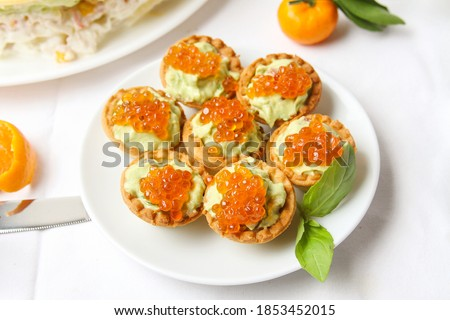 Mini Tartlet With Avocado Cream Decorated Red Salmon Caviar On White Plate With Basil Leaf On The Table. Flat Lay. Stock fotó ©