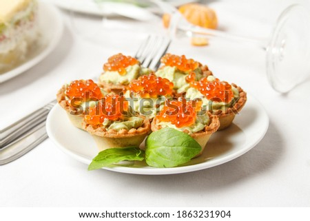 Mini Tartlet With Avocado Cream Decorated Red Salmon Caviar On White Plate With Basil Leaf On The Table. Side View. Stock fotó ©