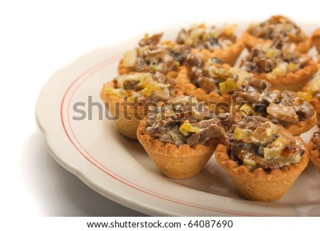 Mini tartlets  with mushrooms, cheese and vegetables on white plate