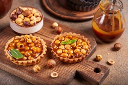 Mini tarts with hazelnuts and caramel cream filling. Sweet homemade dessert.