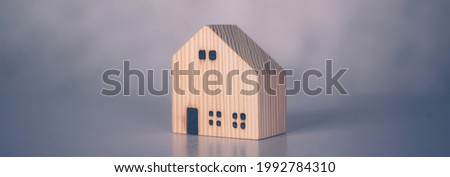 Mini wooden home model concept, investment of real estate and asset, tax of property and rental for finance, no people, small house and inspiration, mortgage and loan for residence, business concept.