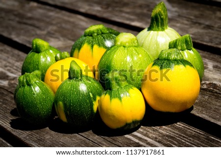 mini zucchini ball eight ball yellow and green over wood table curcurbita pepo