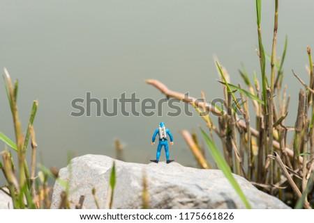 miniature aquanaut stand over the lake