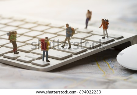 miniature Backpacker Group start journey on keyboard and travel on cyber and internet explorer and soft flare filter