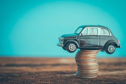 Miniature black second hand car model on coins stack on wooden table. Business, finance or budget plan money saving for buying a used car and auto insurance concept. Road trip for holiday traveling.