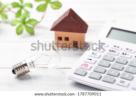 Miniature bulb and calculator on white board