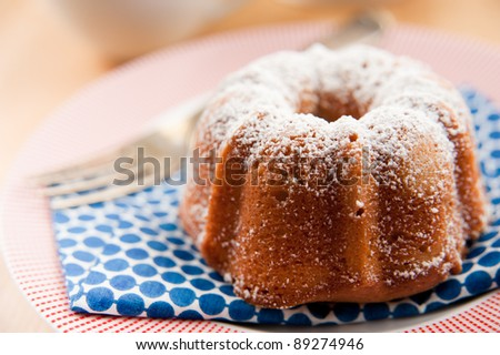 Miniature Bundt Cake Powdered with Sugar and Served with Tea