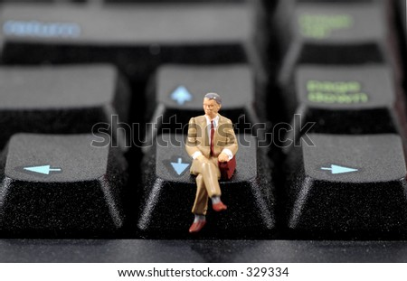Miniature Business Man Sitting on a Keyboard.  Part of Series
