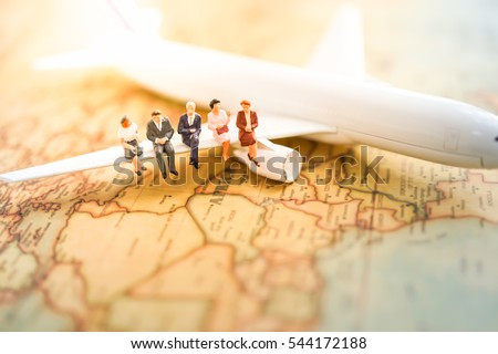 Miniature business people : businesses team sitting on airplane wing for travel around the world, business trip traveler adviser agency or transportation to explorer on earth background concept.