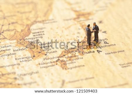 miniature businessman figurines on world map background