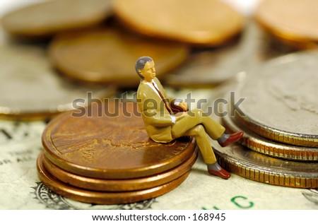 Miniature Businessman Sitting on Pennies. See Portfolio For Similar Concepts