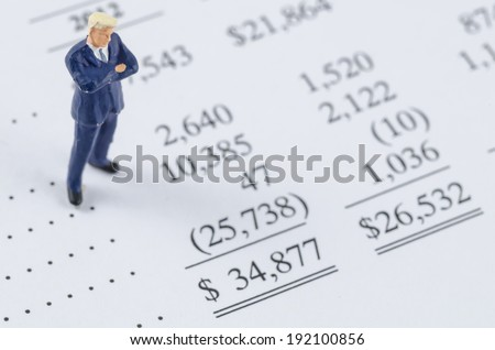miniature businessman standing on the bottom line