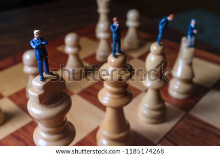 Miniature businessmen battle with giant chesspieces for symbolic metaphor #1185174268