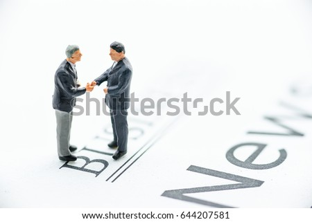 Miniature businessmen greet each other with a warm and firm handshake. Handshake is a short ritual and the act of shaking a person's hand with one's own, used as a greeting or to finalize an agreement #644207581