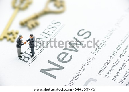 Miniature businessmen greet each other with a warm and firm handshake. Handshake is a short ritual and the act of shaking a person's hand with one's own, used as a greeting or to finalize an agreement #644553976