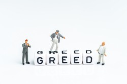 Miniature businessmen standing with cube block building the word Greed on clean white background using as greed and fear in stock market or money game and financial asset.