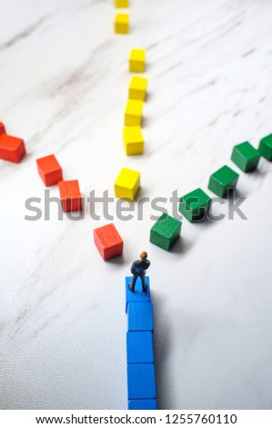 Miniature businessmen trying to pick the path to success down three different wooden block roads #1255760110