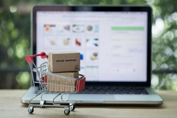 Miniature cardboard boxes in shopping cart with laptop computer. Concept of online shopping