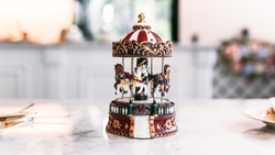 Miniature Carousel Toy over white marble top table with blur background.