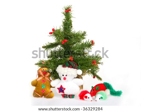 Miniature Christmas tree and cat toys, on white fake snow fabric background