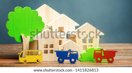 Miniature city. Children's figures and educational games. Wooden houses, trees and vehicles. The concept of urbanization. Growth and development of the urban environment. Traffic load.