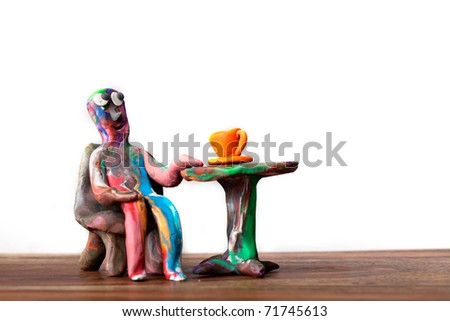 Miniature clay man sitting in cafe with cup of coffee and relaxing