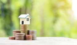 Miniature colorful house on stack coins and nature background using as property, banking and finance concept