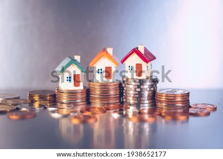 Miniature colorful house on stack coins using as property and financial concept