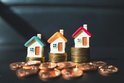 Miniature colorful houses with stack coins on dark background using as property and business concept - Vintage filter