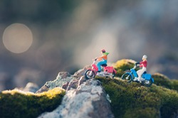 Miniature couple traveling through the countryside on vintage motorcycles at dawn. Macro photography