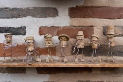 Miniature decoration made from wine cork. Decorative tiny people musician displayed on a brick wall.