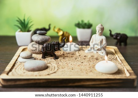 Miniature desk zen sandbox with Buddha figure sit in Lotus position, stacked zen sea stones, brown elephant figurines, spa candles burning against green bokeh studio background, copy space.