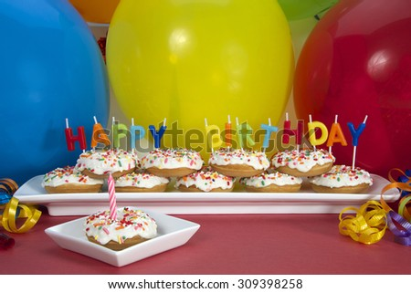 Miniature donut cake on long white plate with happy birthday candles one donut on single square plate with single pink candle. Perfect first birthday party idea for small hands toddler and children